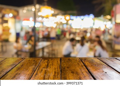 empty wooden table and blurred image of night market food center