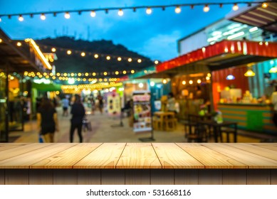 empty wooden table and blurred image of night market for product placement.