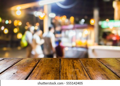empty wooden table and blurred image of people at the street food shop at night