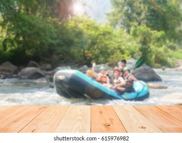 empty wooden table and blurred image of have white water rafting in the river