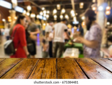 empty wooden table and blurred image of people at the animals show in the night street market