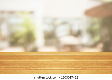 Empty wooden table and blurred modern warm cafe background, restaurants. Ready for product montage, bokeh , light