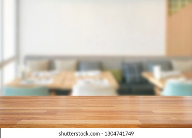 Empty wooden table and blurred modern white kitchen coffee cafe background, restaurants. Ready for product montage, bokeh , light
