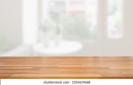 Empty wooden table and blurred modern white kitchen coffee cafe background, restaurants. Ready for product montage