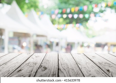 Empty wooden table with blurred party on background,  fun / spring concept