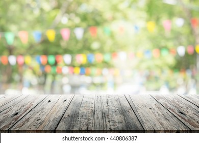 Empty wooden table with blurred party on background. fun / spring concept