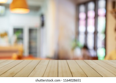 Empty wooden table blurred of restaurant cafe background and reception room, can be used for display or montage your products