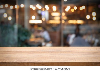 Empty wooden table and blurred restaurant or cafe. Abstract bokeh light. Background concept. Using for Mock up template for display of your design,Banner for advertise of product.