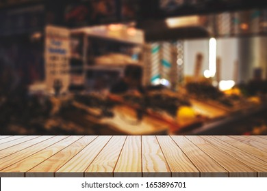 Empty wooden table with blurred restaurant kitchen background.