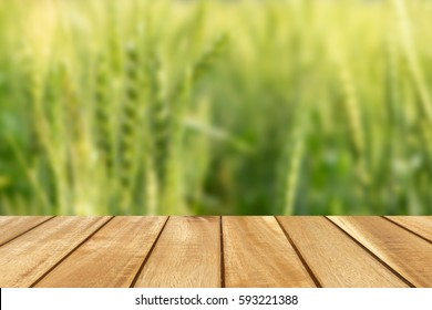 Empty wooden table with blurred of wheat field background