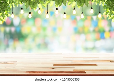 Empty wooden table and bulbs within party in garden background blurred.