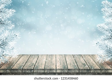 Empty wooden table and Christmas fir trees covered with snow. Snow falls. Blue background.