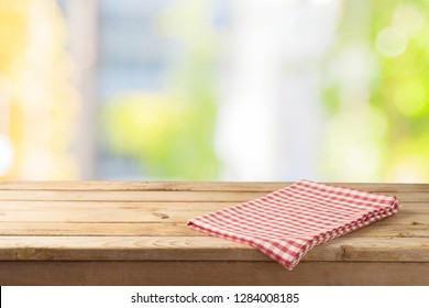 Empty wooden table with table cloth over abstract bokeh background. Mock up for display or montage product