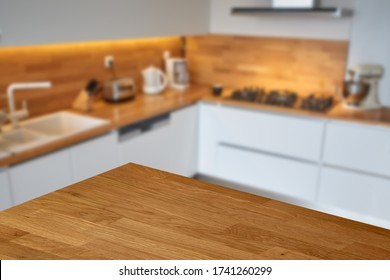 Empty wooden table or countertop top corner with blurred white modern kitchen background.