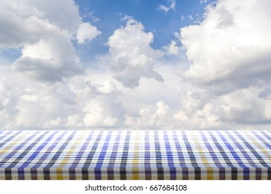 Empty wooden table covered with checkered tablecloth over blue sky and white Cloud background, template, display