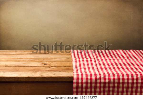 Empty wooden table covered with red checked tablecloth. Background for product montage