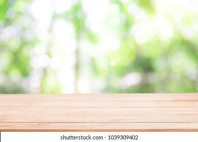 Empty wooden table with Defocus nature green bokeh, abstract nature background with green leaves and bokeh lights.