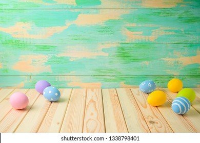 Empty wooden table with Easter eggs over colorful background. Can be used for food stand, key visual layout or new product advertising display