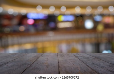 Empty wooden table in front of abstract blurred background of shopping mall and people . can be used for display or montage your products. Mock up for display of product - Image