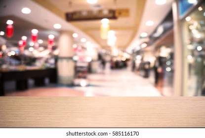 Empty wooden table  in front of abstract blurred background of shopping mall and people . can be used for display or montage your products.Mock up for display of product