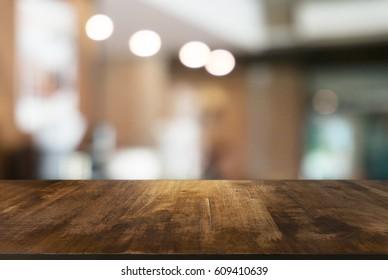 Leerer Holztisch vor abstraktem, unscharfem Hintergrund des Kaffeehauses . kann zur Anzeige oder Montage Ihrer Produkte verwendet werden.Mock up for display of product