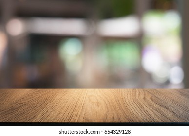 Empty wooden table in front of abstract blurred background of coffee shop . can be used for display or montage your products.Mock up for display of product