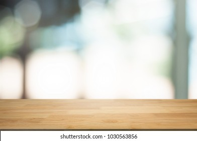 empty wooden table in front of blur montage abstract background