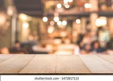 Empty wooden table in front of Blur background of coffee shop or restaurant interior abstract. Using for Mock up template for display of your design or montage  products.