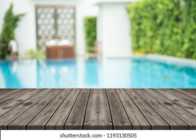 Empty wooden table in front with blurred background of swimming pool