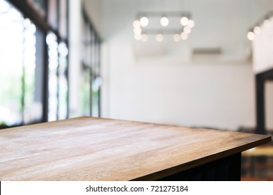 empty wooden table in front of blurred coffee shop cafe or workplace background