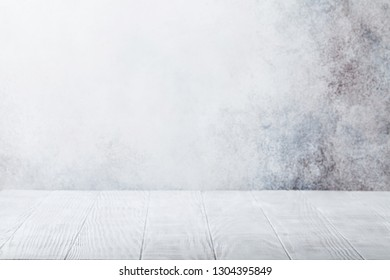 Empty wooden table in front of stone wall. With copy space