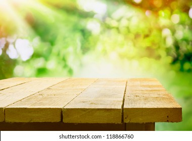 Empty wooden table with garden bokeh for a catering or food background with a country outdoor theme