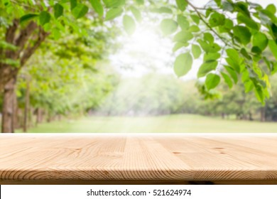 Empty wooden table with garden bokeh for a catering or food background with a country outdoor theme,Template mock up for display of product