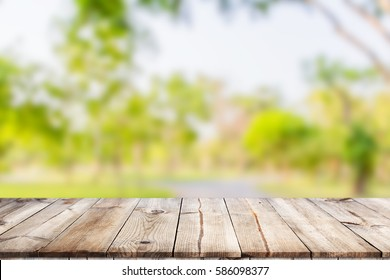 Empty wooden table with garden bokeh for a catering or food background with a country outdoor theme / Template mock up for display of product
