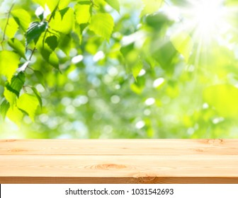 Empty wooden table on a background of spring bright foliage.