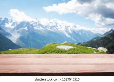 Empty wooden table on the background of scenic mountain Alpine landscape. Template for montage