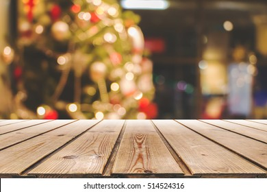 Empty wooden table on a background of the Christmas charts,background of free space for you with wooden desk and balls and tree