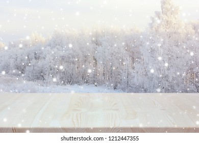Empty wooden table on blurred winter backdrop. Empty space for Your object. Light background, table layout with winter trees and snowflakes.