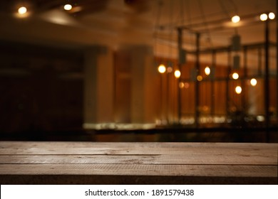 empty wooden table on blurred light gold bokeh of cafe restaurant on dark background, place for your products on the table