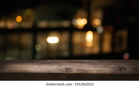 empty wooden table on blurred light gold bokeh of window cafe restaurant on dark background, place for your products on the table