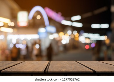 Empty wooden table on front blurred colorful night street background, copy space for presentation product