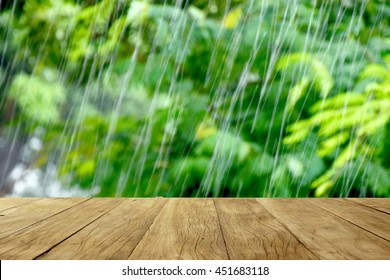 Empty wooden table on green trees in rainy nature background