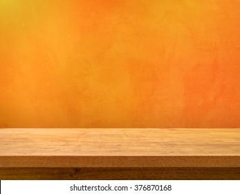 Empty wooden table on orange textured wall