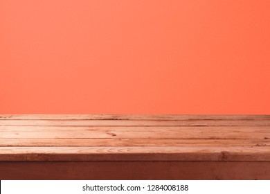 Empty wooden table with over abstract coral color wall background. Mock up for display or montage product