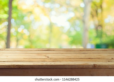 Empty wooden table over autumn nature bokeh background