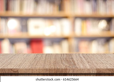 Empty wooden table over blur book shelves background, education concept, template, product display montage