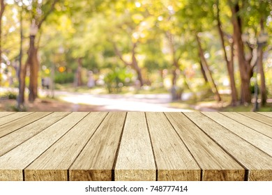 Empty wooden table over blur nature park outdoor background, blank tabletop design for product display montage template