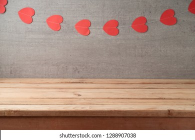 Empty wooden table over rustic wall background with heart shape garland. Valentine's day concept celebration.