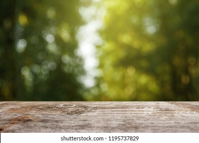 An empty wooden table overlooking a blurred green bokeh background, copy space for your text. Creative background, place for installation. Nature concept