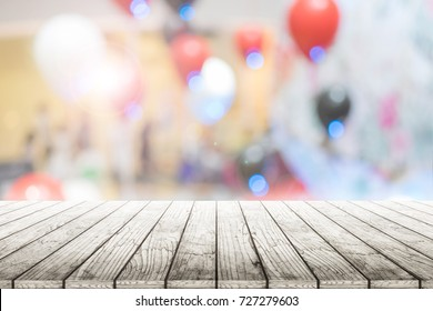 Empty wooden table with party in wedding background blurred.